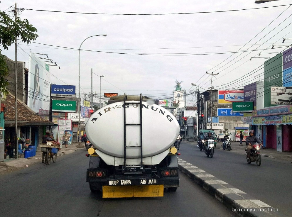 """A tanker truck strolling down the street near Ujungberung square, a peri-urban district of Bandung City. """"Hidup tanpa air mati"""" or """"to live without water is death"""" is written in the lower body of the truck. This truck delivers """"air gunung"""" or """"mountain water"""" from commercialized springs to refill water kiosks. Local entrepreneurs had become the main provider of water for the peri-urban people in this part of the city (photo: Anindrya Nastiti)"""